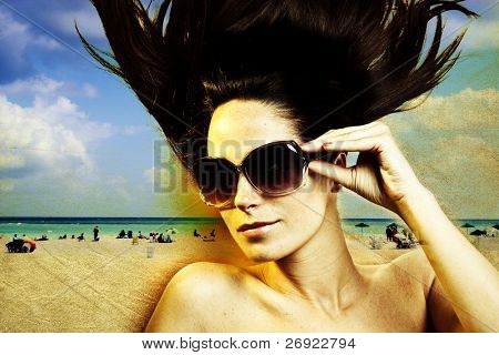 Fashion shot of a beautiful woman at the beach, focus on sunglasses