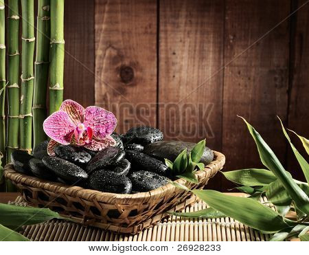 composition bamboo grove, pink orchid and black zen stones in the bowl on the wooden background