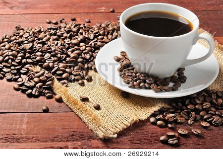 white cup with coffee beans on the wooden table