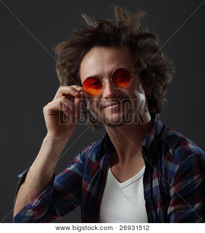 Smiling man with round hippie sunglasses and long funny hair