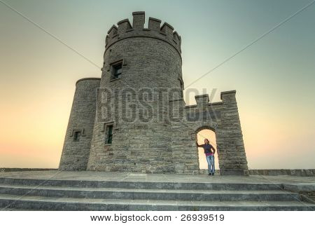 Woman at OBriens Tower on Cliffs of Moher at sunset