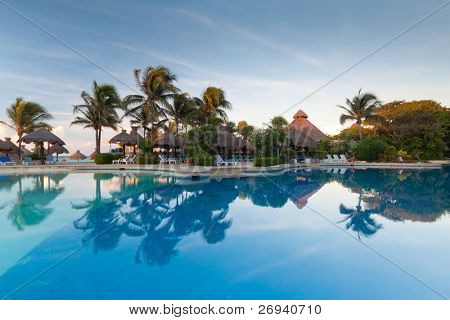 Tropical swimming pool at sunrise in Mexico