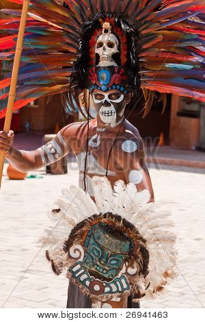 TULUM, MEXICO - JULY 15: Unidentified man in Mayan traditional ornamental feather headdress dances to please the rain god Xipe Totec on July 15, 2011 in Tulum, Quintana Roo, Mexico