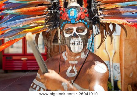 TULUM, MEXICO - JULY 15: Unknown man in Mayan traditional ornamental feather headdress playing on drums to the ritual pleased the rain god Xipe Totec. July 15, 2011 in Tulum, Quintana Roo, Mexico