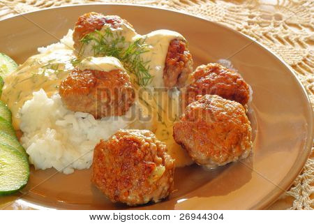 Beef meatballs with white dill sauce served on rice