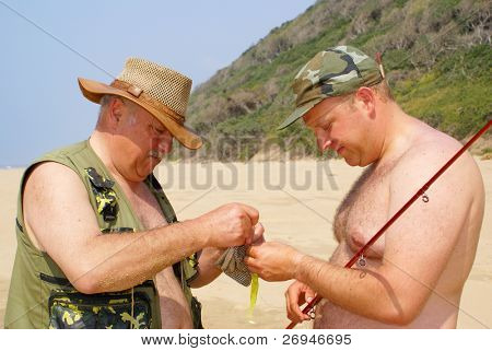 Father and son preparing fishing gear