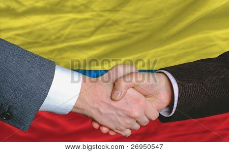 Businessmen Handshakeafter Good Deal In Front Of Columbia Flag