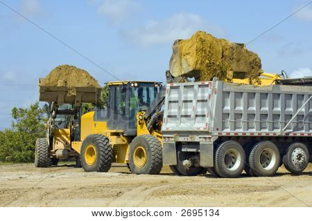 A Pair Of Front End Loaders Filling A Dump Truck