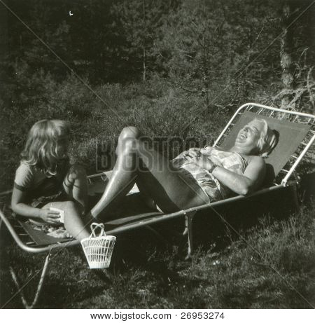 Vintage photo of mother and daughter on camping bed (fifties)