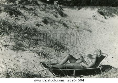 vintage unretouched photo of woman tanning on camping bed
