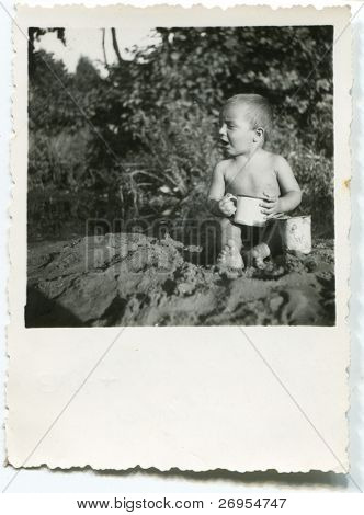 Vintage unretouched photo of baby boy playing in sand (early forties)