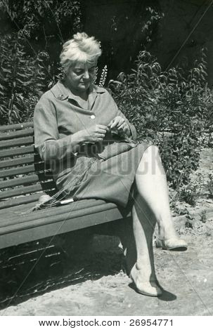 Vintage unretouched photo of woman knitting on bench in park (fifties/sixties)