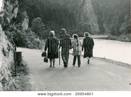 Vintage photo of happy three generations family walking