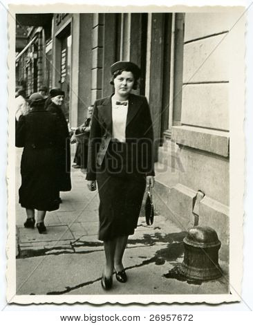 Vintage photo of young woman walking on the street (thirties)