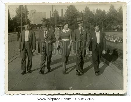 Vintage photo of  father, uncle, sons and daughter walking on the street (thirties)
