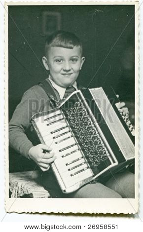 Vintage photo of boy playing an accordion (fifties)
