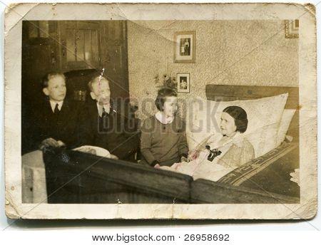 Vintage photo of family visiting bedridden grandmother