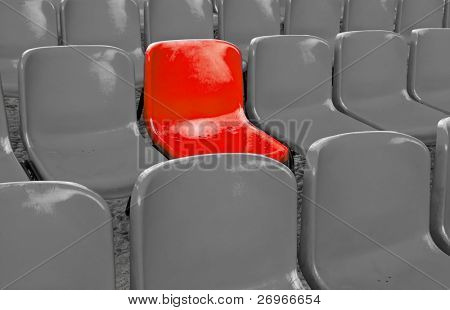 A single red chair in a multitude of grey ones