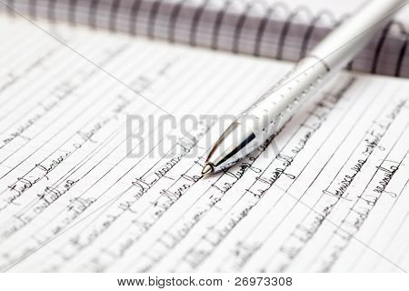 A silver pen lying on a notebook in the office