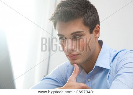 A portrait of a young handsome businessman being thoughtful looking at his laptop, with a ray of light from the window in the background