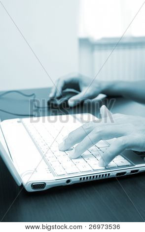 Blue toned image of male hands typing on a computer keyboard