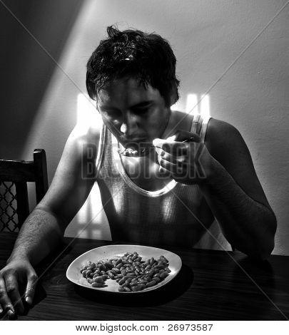 Fazendeiro cansado, ter um jantar frugal em sua casa iluminada pela luz solar passada de um dia duro de w