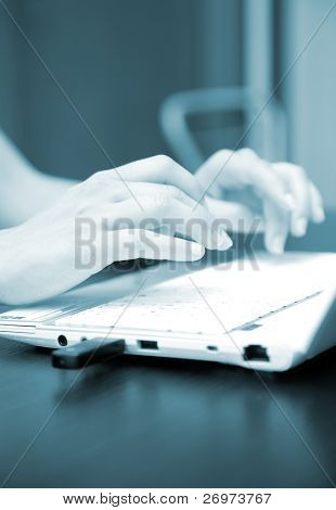 Blue toned image of a woman typing on the keyboard