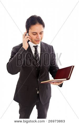 Businessman talking at the mobile phone while looking at his agenda