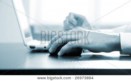 Closeup of male hands typing on a laptop and moving a mouse - blue toned image