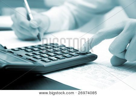 Businessman working in his office with his calculator, blue toned image