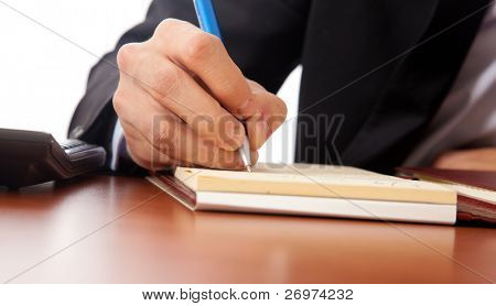 Stock Photo: Businessman writing some documents on a wood desk