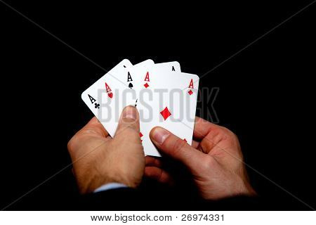 Man holding four aces in hands isolated on black background