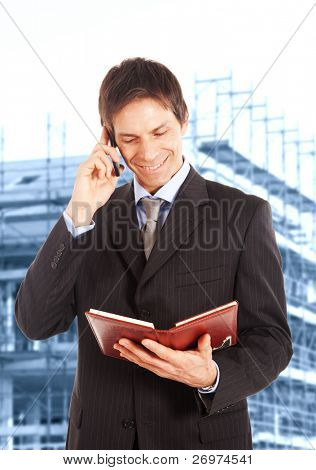 Portrait of a building contractor near a construction site, while talking at phone and reading something on his agenda. Blue toned background, focus on subject.