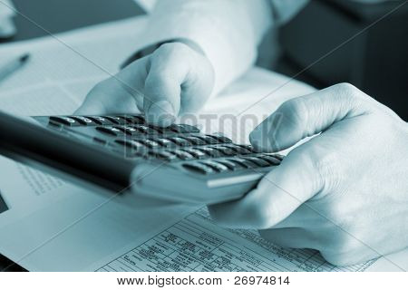 Businessman holding a calculator - blue toned image
