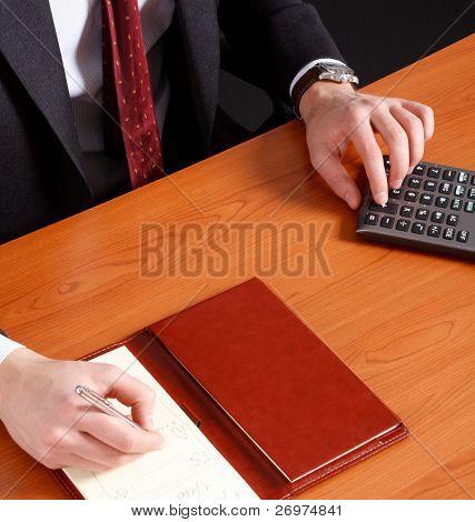 Un hombre de negocios haciendo algunos trámites usando su calculadora