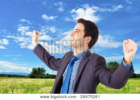 Young businessman raising his hands in sign of victory