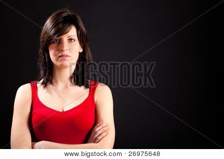 Beautiful serious young caucasian girl on dark background