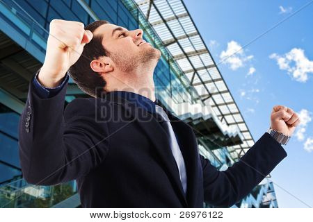 Young businessman standing with fists clenched in victory.