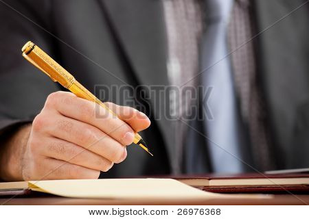 Businessman writing some documents on a wood desk in low light