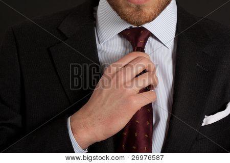 Businessman adjusting his look on a dark background