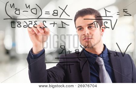 Young businessman writing math formulas on the screen.