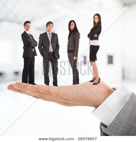 Big businessman holding people on his hand.