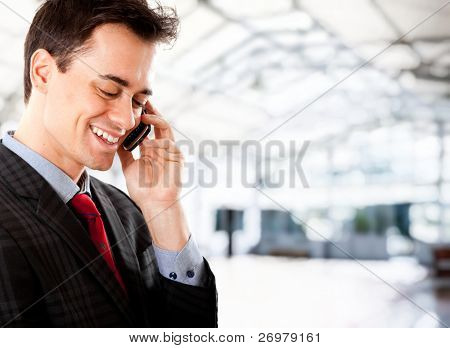 Young man on the phone at the airport saying goodbye to his partner while leaving for business