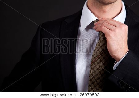 Businessman adjusting his collar on a dark background