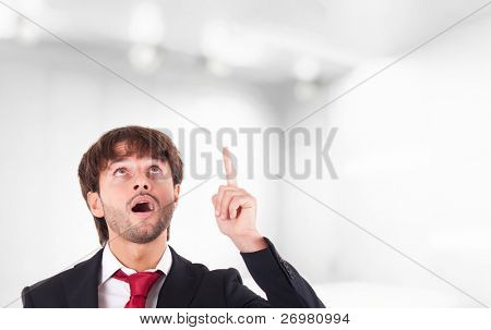 Portrait of an handsome businessman looking and pointing his finger up