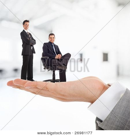 Big businessman holding businesspeople on his hand.