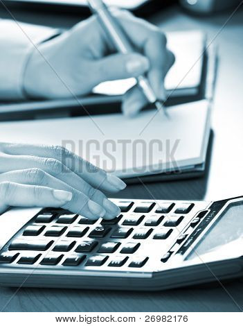 Businesswoman working on her desk in the office, blue toned image