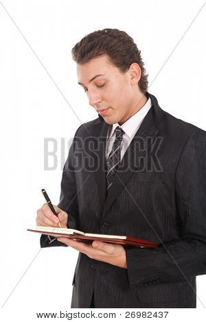 Young businessman writing something on his agenda. Isolated against white background.