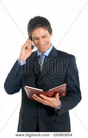 Mature businessman reading his agenda while on the phone
