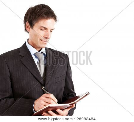 Mature businessman writing something on his agenda. Isolated against white background.